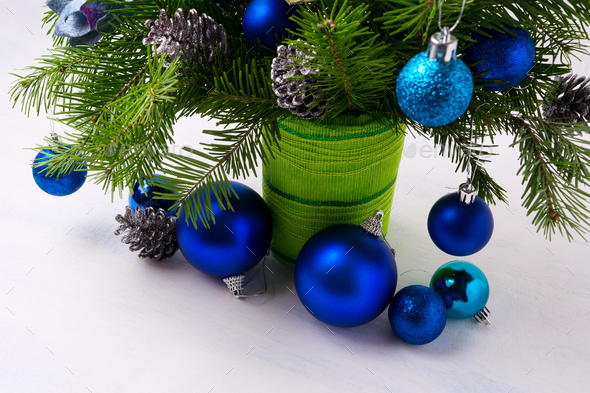 Christmas centerpiece with blue ornaments and fir branches in gr - Stock Photo - Images