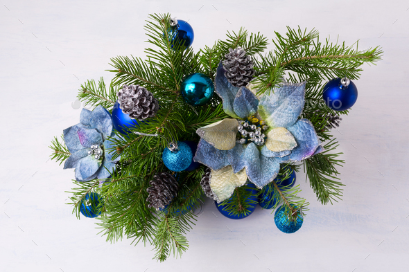 Christmas centerpiece with glitter baubles, blue silk poinsettia - Stock Photo - Images