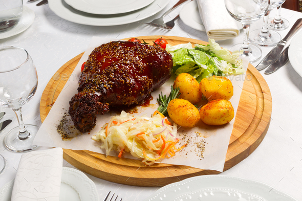 Meat with garnish of vegetables on a wooden board - Stock Photo - Images