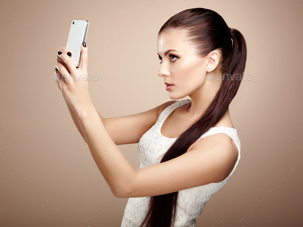 Beautiful young woman taking selfie - Stock Photo - Images
