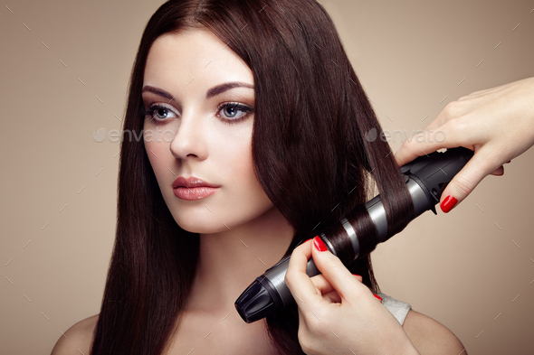Hairdresser woman curls her hair - Stock Photo - Images