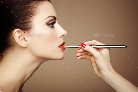 Makeup artist applies lipstick - Stock Photo - Images