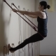 Young and Pretty Lady Performs an Inverted Asana Using Ropes, a Lady Engaged in Patta Yoga