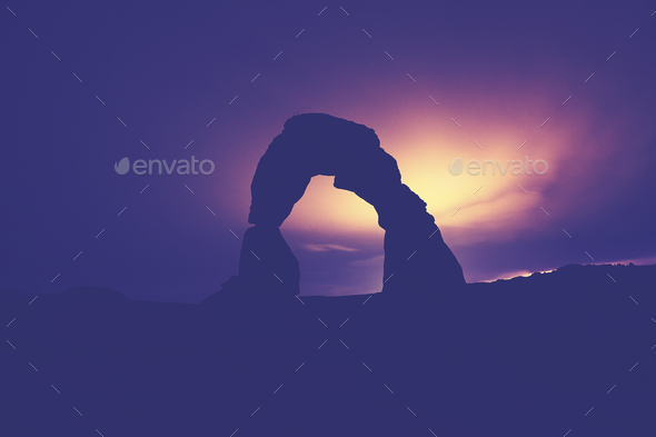 Moonlight backlit Delicate Arch silhouette, USA. - Stock Photo - Images