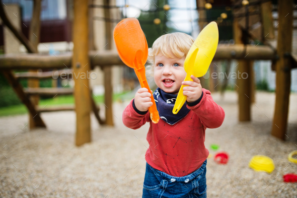 Toddler boy playing in the playground, summer day. - Stock Photo - Images