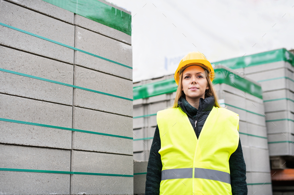 Woman worker standing in an industrial area. - Stock Photo - Images