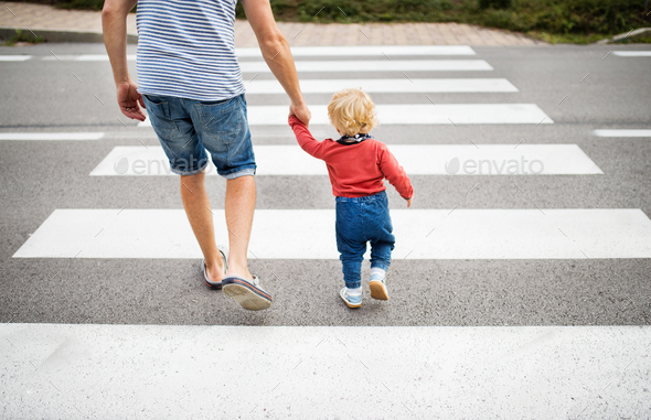 Father with little boy crossing the road on crosswalk. - Stock Photo - Images