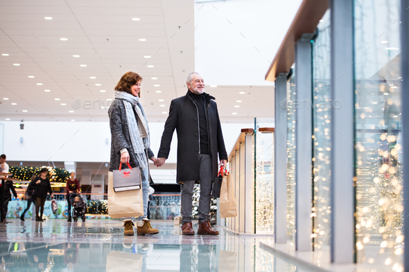 Senior couple doing Christmas shopping. - Stock Photo - Images