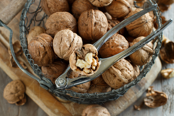 Fresh walnuts in basket on rustic old wooden table - Stock Photo - Images