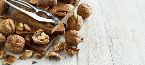 Fresh walnuts with a nutcracker on an old wooden table - Stock Photo - Images