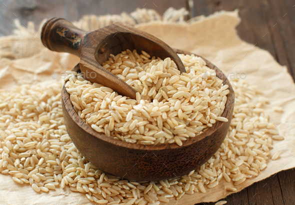 Pile of Brown rice in a bowl with a wooden spoon - Stock Photo - Images