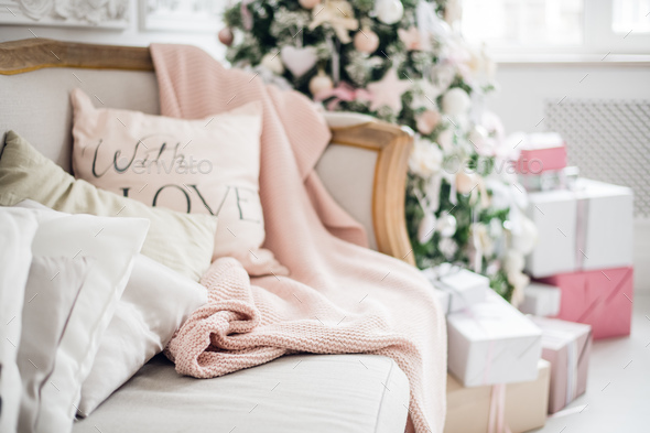christmas coziness christmas tree, pillows on a couch feather pink veil blanket of thick yarn - Stock Photo - Images