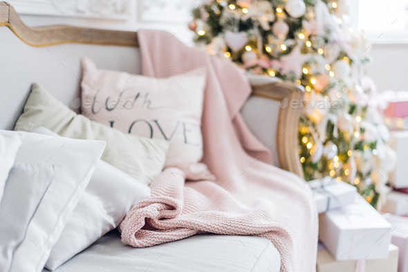 Knitted plaid and pillows on a sofa at home on a christmas eve. Home cosiness - Stock Photo - Images