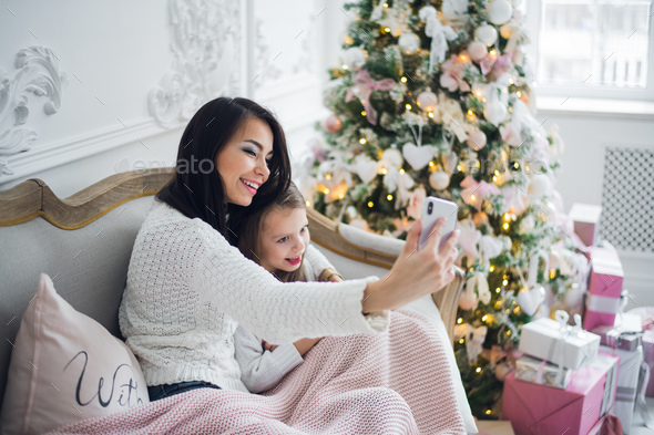 Well-groomed hand of a woman holding a phone taking a selfie with her daughter, little girl - Stock Photo - Images