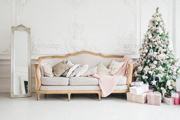 Christmas tree with a white sofa in a white room. - Stock Photo - Images