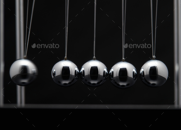Closeup Of Newton Cradle With Swinging Metal Balls - Stock Photo - Images