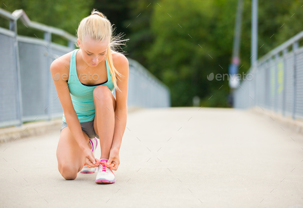 Young woman runner tying shoelaces on bridge - Stock Photo - Images
