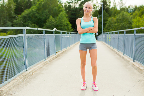 Confident and smiling young female runner having break after workout - Stock Photo - Images