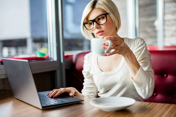 Young Woman Having Coffee While Working On Laptop In Cafe - Stock Photo - Images