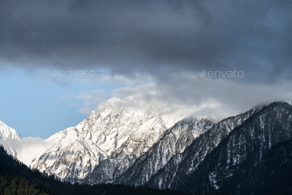 snow capped mountain and misty clouds - Stock Photo - Images