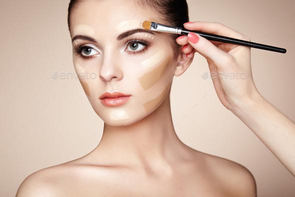 Makeup artist applies skintone - Stock Photo - Images