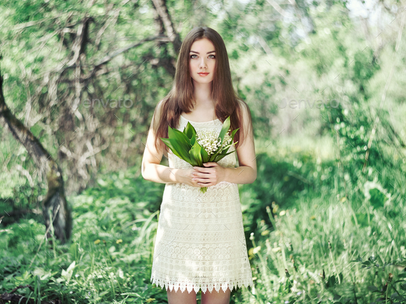 Portrait of beautiful young woman with lily of the valley - Stock Photo - Images
