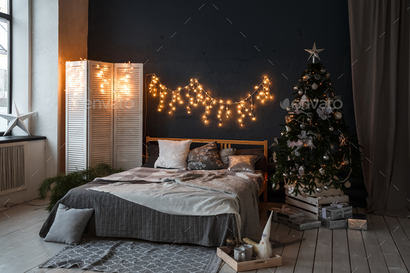 A spacious bedroom in a loft style with a decorated Christmas tree and a garland. - Stock Photo - Images