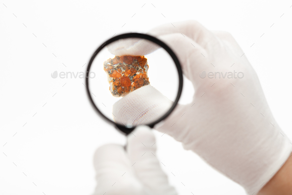master inspects spessartine garnets with magnifier - Stock Photo - Images