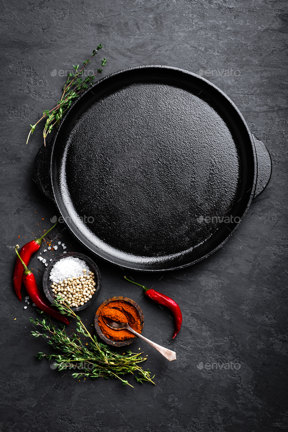 Empty cast-iron pan with ingredients for cooking on black background, top view - Stock Photo - Images
