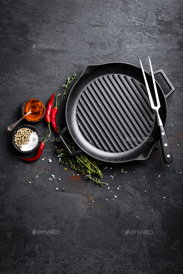 Empty cast-iron grill pan with ingredients for cooking on black background, top view - Stock Photo - Images
