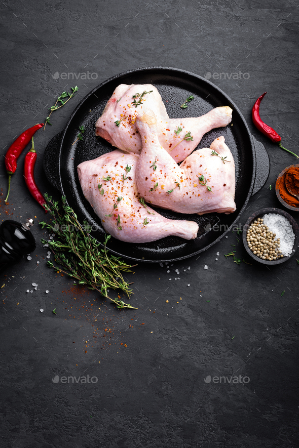 Raw chicken quarters, legs in a pan on a dark background. Top view. - Stock Photo - Images