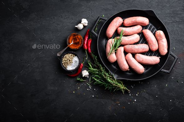Fresh raw sausages on a cast-iron grill pan on a black background, top view - Stock Photo - Images