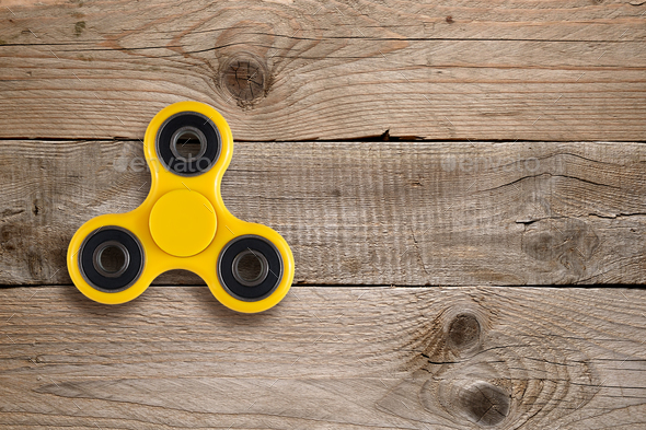 Fidget spinner toy on wooden table - Stock Photo - Images