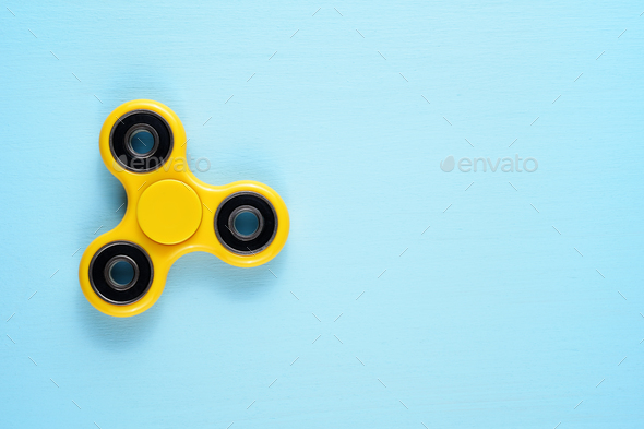 Fidget spinner toy on blue background - Stock Photo - Images