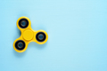 Fidget spinner toy on blue background - PhotoDune Item for Sale