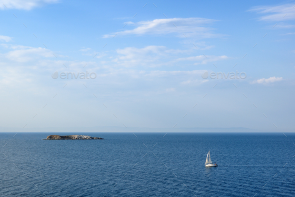 Seascape with sailing yacht and small island in sea - Stock Photo - Images