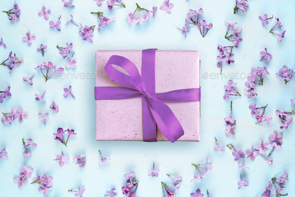 Gift box and lilac flowers on blue background - Stock Photo - Images