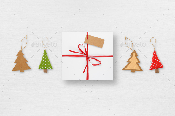 Gift box with tag and christmas tree decorations on white table top view - Stock Photo - Images
