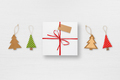 Gift box with tag and christmas tree decorations on white table top view - PhotoDune Item for Sale