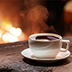 Cup of Coffee stands on an Old Wooden Board in Front of a Burning Fireplace - VideoHive Item for Sale