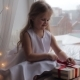 Young Girl Unpacking Her Present and Sitting on a Windowsill - VideoHive Item for Sale
