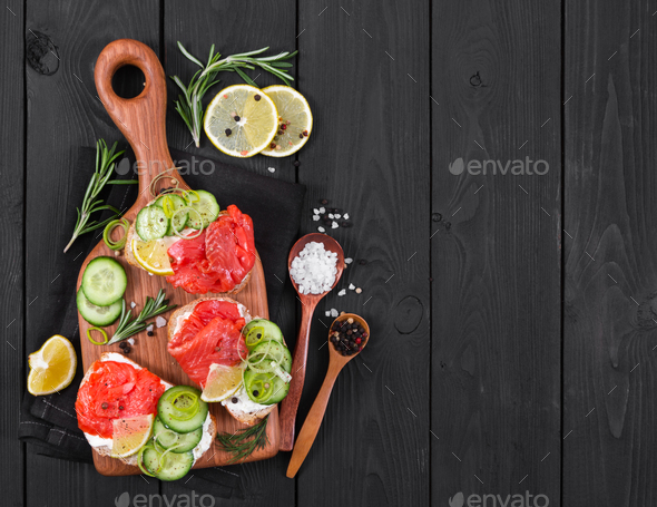Bruschetta with salmon and fresh cucumber on cutting board - Stock Photo - Images