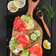 Bruschetta with salmon and fresh cucumber on cutting board - PhotoDune Item for Sale