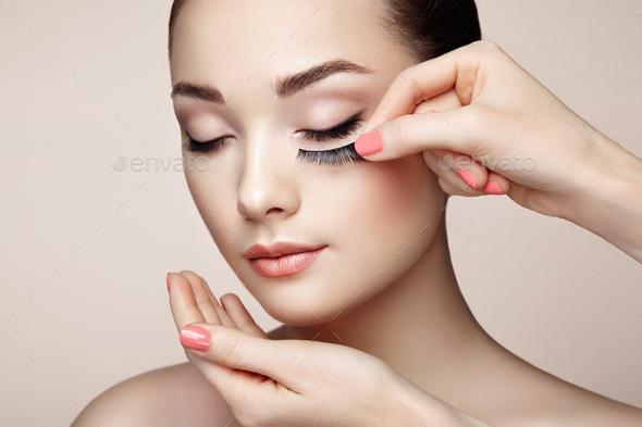 Makeup artist glues eyelashes - Stock Photo - Images