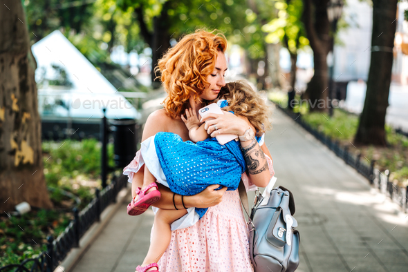 Woman hugs her daughter, holding her in her arms - Stock Photo - Images