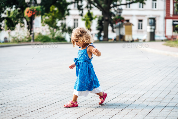 Beautiful little girl walking in the sun - Stock Photo - Images
