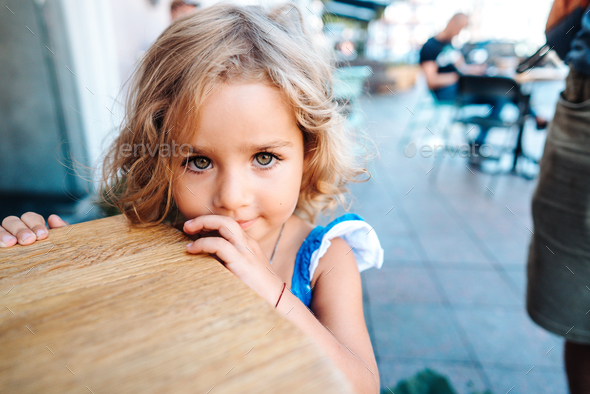 Little girl in a blue dress near a small table - Stock Photo - Images