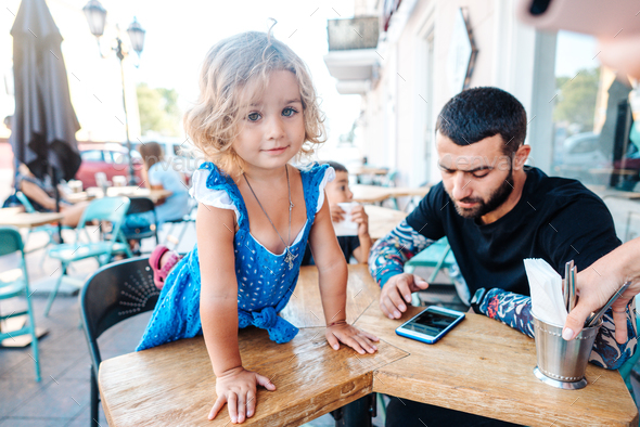 Dad and little daughter are sitting in a cafe - Stock Photo - Images
