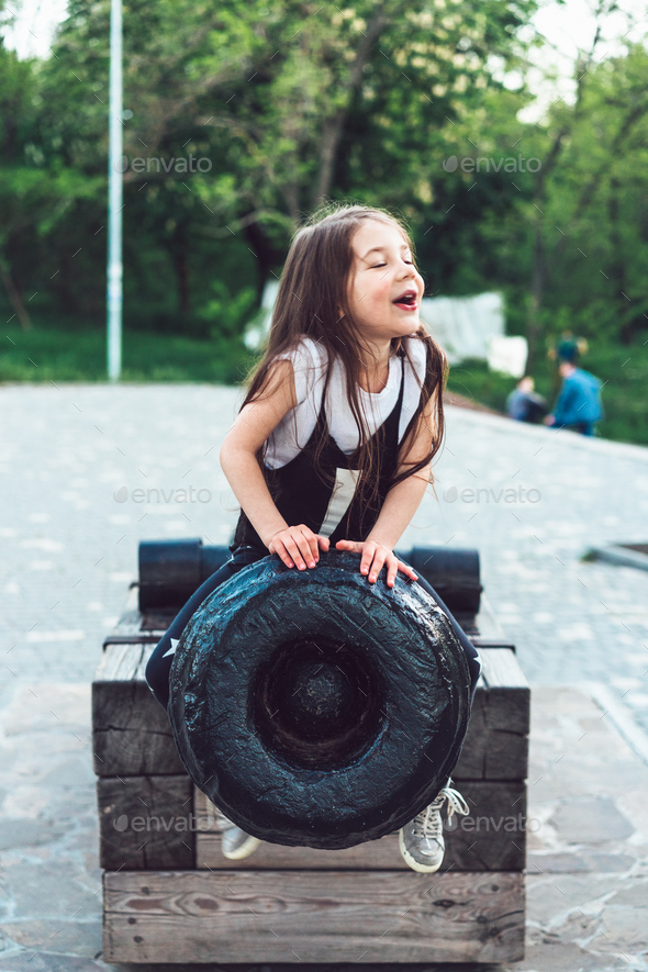 preschool girl sitting on top of a cannon - Stock Photo - Images