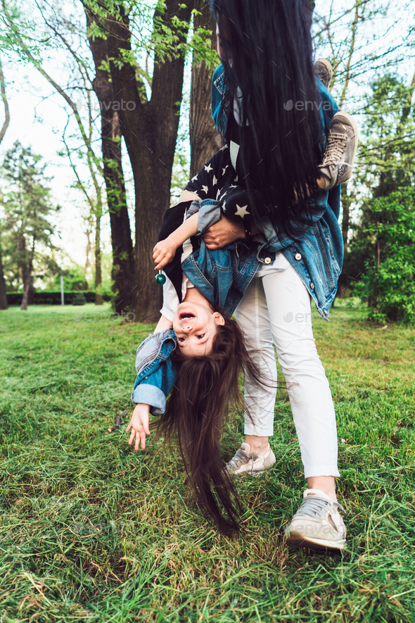 mom and daughter on the lawn have fun - Stock Photo - Images